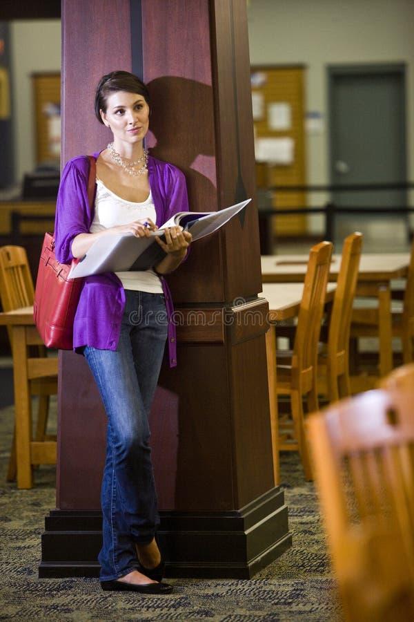 Θηλυκός φοιτητής πανεπιστημίου που στέκεται στη βιβλιοθήκη στοκ εικόνα με δικαίωμα ελεύθερης χρήσης