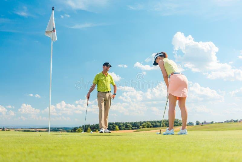 Θηλυκός φορέας γκολφ έτοιμος να χτυπήσει τη σφαίρα στοκ εικόνες