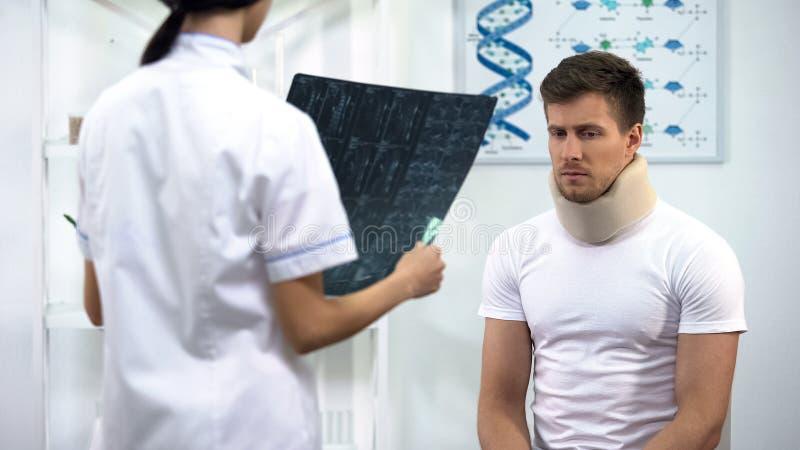 Θηλυκός χειρούργος που ενημερώνει τον ασθενή στο αυχενικό περιλαίμιο αφρού για το κακό των ακτίνων X αποτέλεσμα στοκ φωτογραφίες