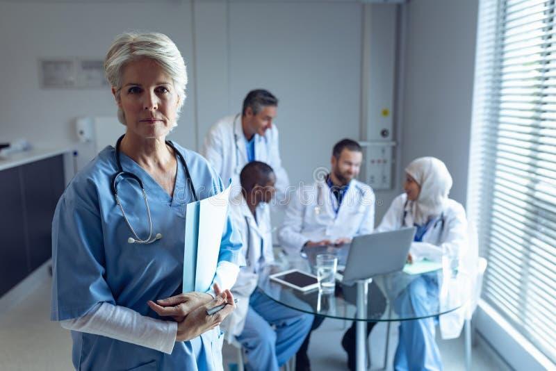 Θηλυκός χειρούργος που στέκεται με το ιατρικό αρχείο ενώ γιατροί που αλληλεπιδρούν ο ένας με τον άλλον στο backgroun στοκ εικόνα με δικαίωμα ελεύθερης χρήσης