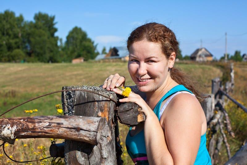 Θηλυκός χωρικός που στέκεται μπροστά από την ξύλινη φραγή στοκ φωτογραφία
