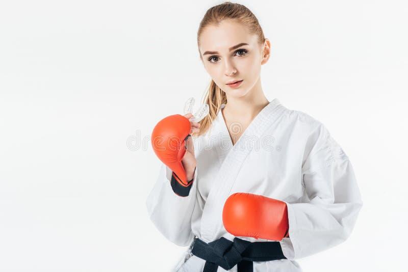 θηλυκός karate μαχητής που εξετάζει τη κάμερα με το mouthguard και τα γάντια στοκ φωτογραφία