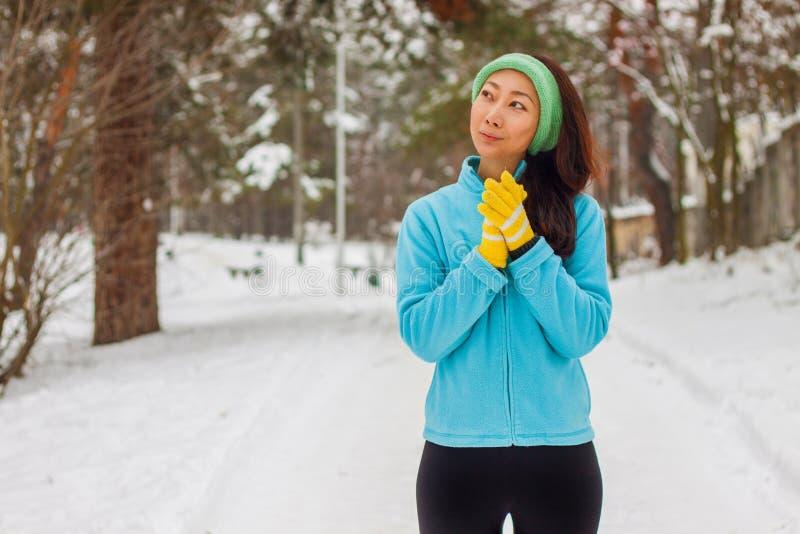 Θηλυκό ίχνος δρομέων που τρέχει στον κρύο χιονίζοντας καιρό E στοκ φωτογραφίες