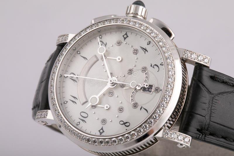 Θηλυκό ασημένιο ρολόι με έναν άσπρο πίνακα, ασήμι δεξιόστροφα, chronograph, χρονόμετρο με διακόπτη, διαμόρφωση των πετρών, με ένα στοκ εικόνα