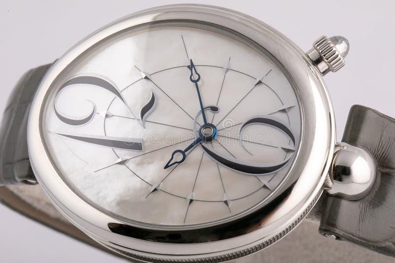 Θηλυκό ασημένιο ρολόι με έναν γκρίζο πίνακα, μπλε δεξιόστροφα, με ένα μαύρο λουρί δέρματος στοκ εικόνες