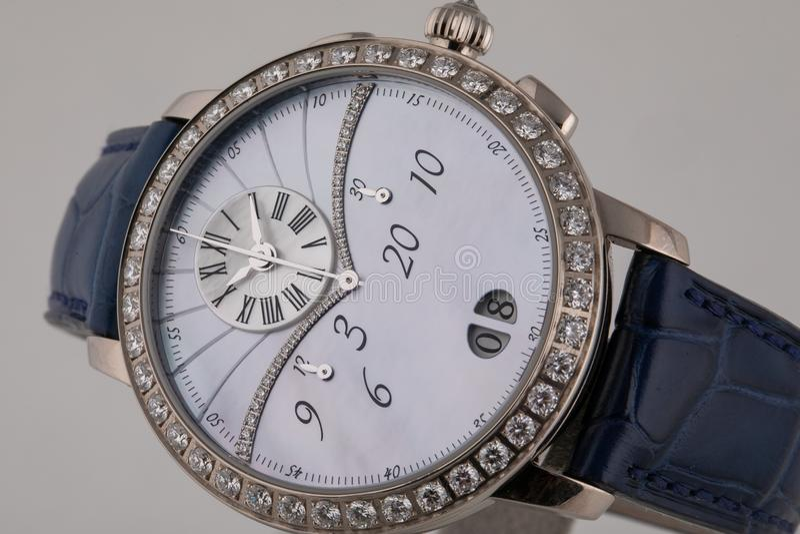 Θηλυκό ασημένιο wristwatch με τον άσπρο πίνακα, ασήμι δεξιόστροφα με chronograph στο μπλε λουρί δέρματος που απομονώνεται στο άσπ στοκ εικόνες