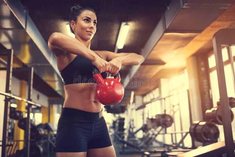 Θηλυκό βάρος κουδουνιών κατσαρολών χρήσης για την άσκηση των μυών στοκ φωτογραφίες