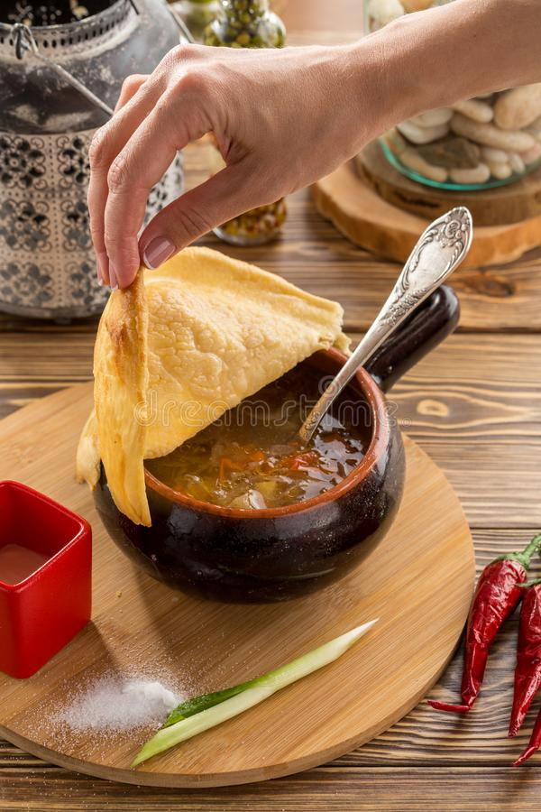 Θηλυκό καπάκι ψωμιού εκμετάλλευσης χεριών στη ρωσική σούπα shchi λάχανων με το βόειο κρέας στο δοχείο αργίλου στον ξύλινο πίνακα στοκ εικόνες