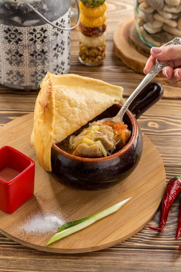 Θηλυκό κουτάλι εκμετάλλευσης χεριών με τη ρωσική σούπα shchi λάχανων με το βόειο κρέας στο δοχείο αργίλου στον ξύλινο πίνακα στοκ εικόνα με δικαίωμα ελεύθερης χρήσης