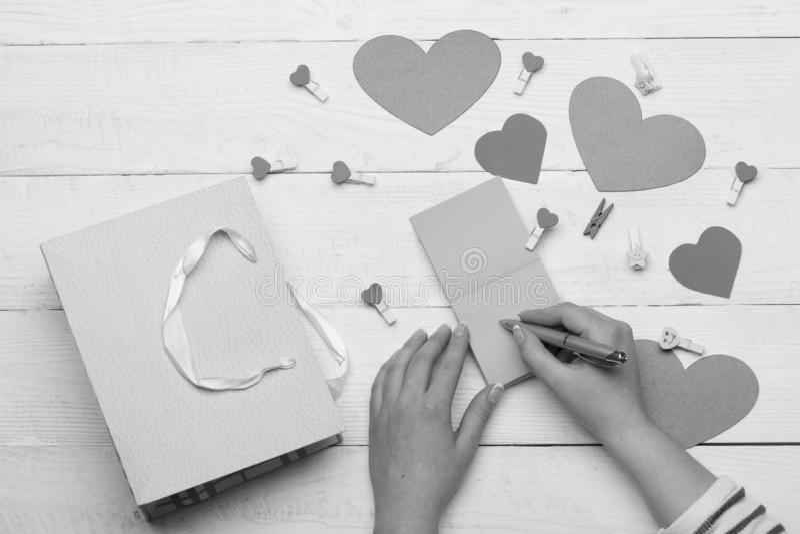 Θηλυκό μήνυμα αγάπης γραψίματος χεριών σε ρόδινο χαρτί σημειώσεων στοκ εικόνα με δικαίωμα ελεύθερης χρήσης