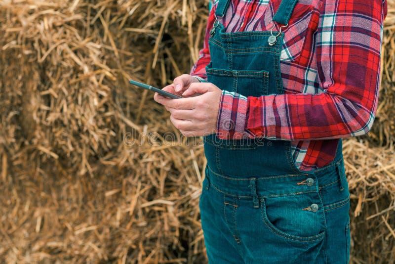 Θηλυκό μήνυμα δακτυλογράφησης αγροτών sms στο κινητό τηλέφωνο στοκ φωτογραφίες με δικαίωμα ελεύθερης χρήσης