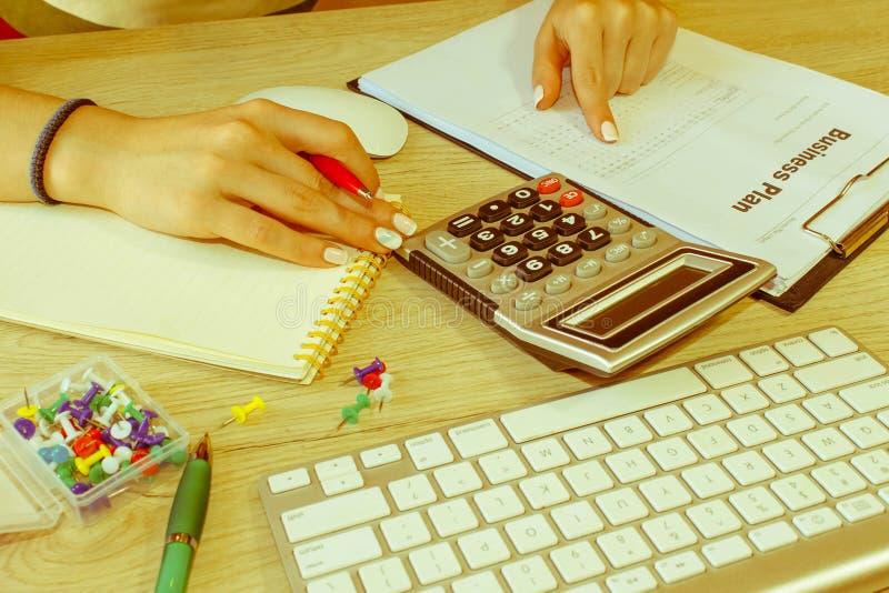 Θηλυκό με το επιχειρηματικό σχέδιο, τον υπολογιστή και τη μάνδρα στον πίνακα Εργασία γυναικών στην αρχή, καθμένος στο γραφείο, πο στοκ φωτογραφίες με δικαίωμα ελεύθερης χρήσης