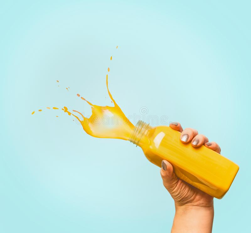Θηλυκό μπουκάλι εκμετάλλευσης χεριών με το κίτρινο θερινό ποτό παφλασμών: καταφερτζής ή χυμός στο μπλε στοκ φωτογραφία με δικαίωμα ελεύθερης χρήσης