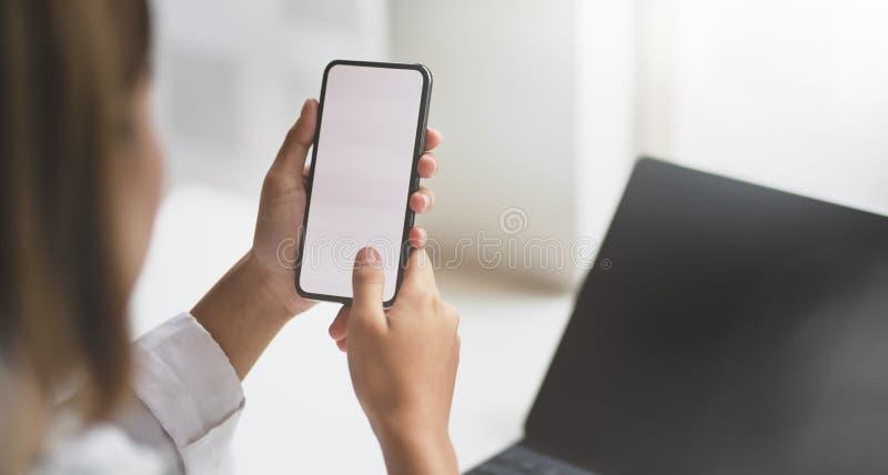 Θηλυκό ξεκίνημα που ψάχνει για τις νέες πληροφορίες για το smartphone στοκ φωτογραφία με δικαίωμα ελεύθερης χρήσης