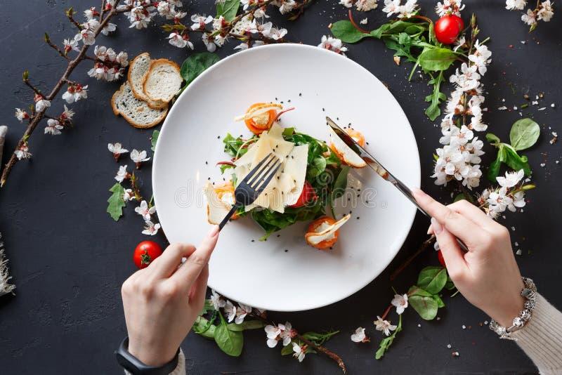 Θηλυκό πιάτο εστιατορίων κατανάλωσης στο άσπρο πιάτο στο γκρίζο υπόβαθρο στοκ φωτογραφία με δικαίωμα ελεύθερης χρήσης