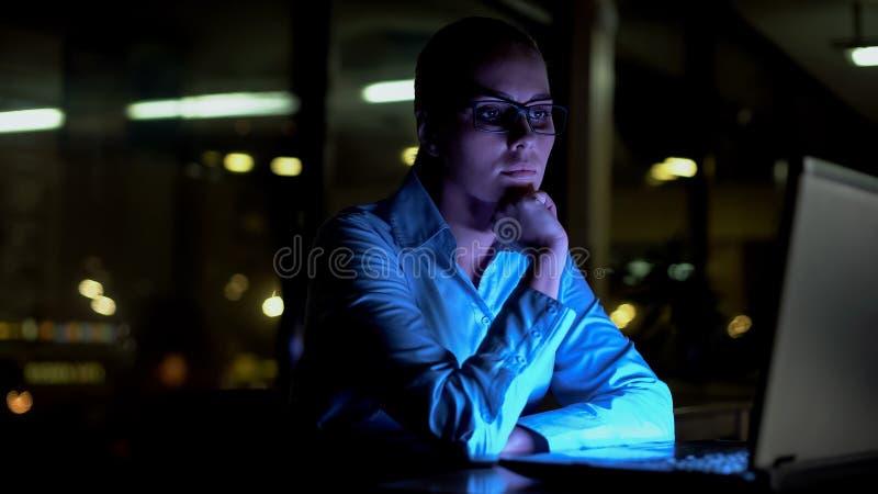 Θηλυκό που απασχολείται στις πρόσθετες ώρες τη νύχτα, που σκέφτονται πέρα από το δύσκολο επιχειρησιακό πρόγραμμα στοκ φωτογραφία