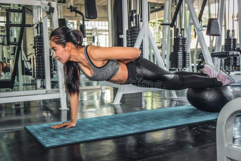 Θηλυκό που επιλύει με την ώθηση επάνω στη γυμναστική στοκ εικόνες