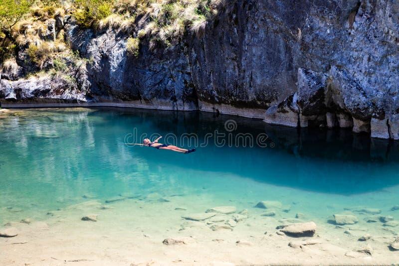 Θηλυκό που επιπλέει στις φυσικές μπλε λίμνες στοκ εικόνα με δικαίωμα ελεύθερης χρήσης