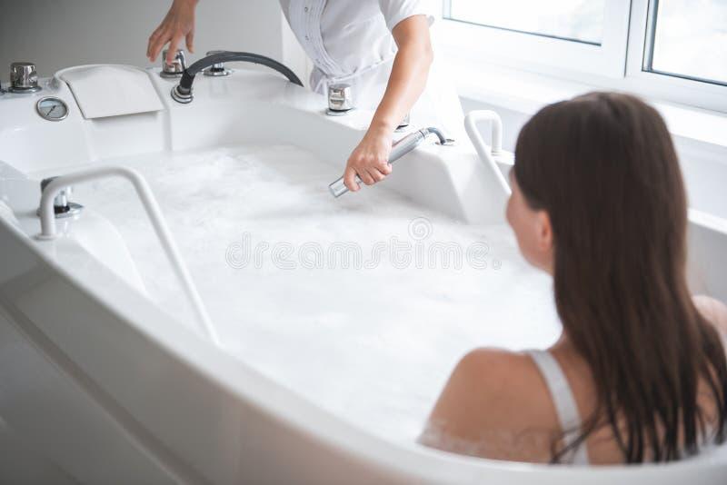 Θηλυκό που στηρίζεται στο νερό στο κέντρο SPA στοκ εικόνες