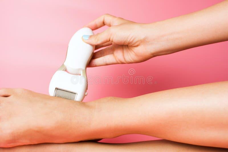 Θηλυκό που τρίβει το σκληρό δέρμα από τα πόδια στοκ εικόνα