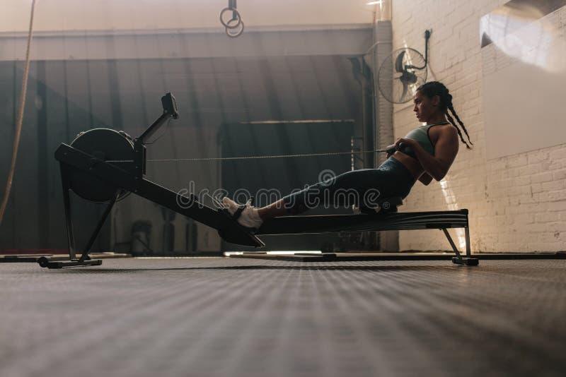 Θηλυκό που χρησιμοποιεί τη μηχανή κωπηλασίας στη λέσχη υγείας στοκ φωτογραφία με δικαίωμα ελεύθερης χρήσης