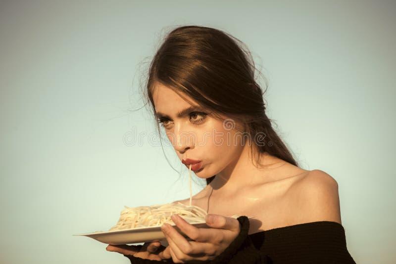 Θηλυκό πρόσωπο Ζητήματα που έχουν επιπτώσεις στα κορίτσια Κατανάλωση των νόστιμων ζυμαρικών στο ηλιόλουστο υπόβαθρο μπλε ουρανού στοκ φωτογραφία