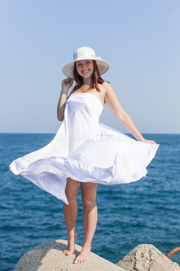Θηλυκό πρόσωπο στο άσπρο καπέλο και τα άσπρα σαρόγκ που θέτουν ενάντια στη θάλασσα στοκ εικόνα με δικαίωμα ελεύθερης χρήσης