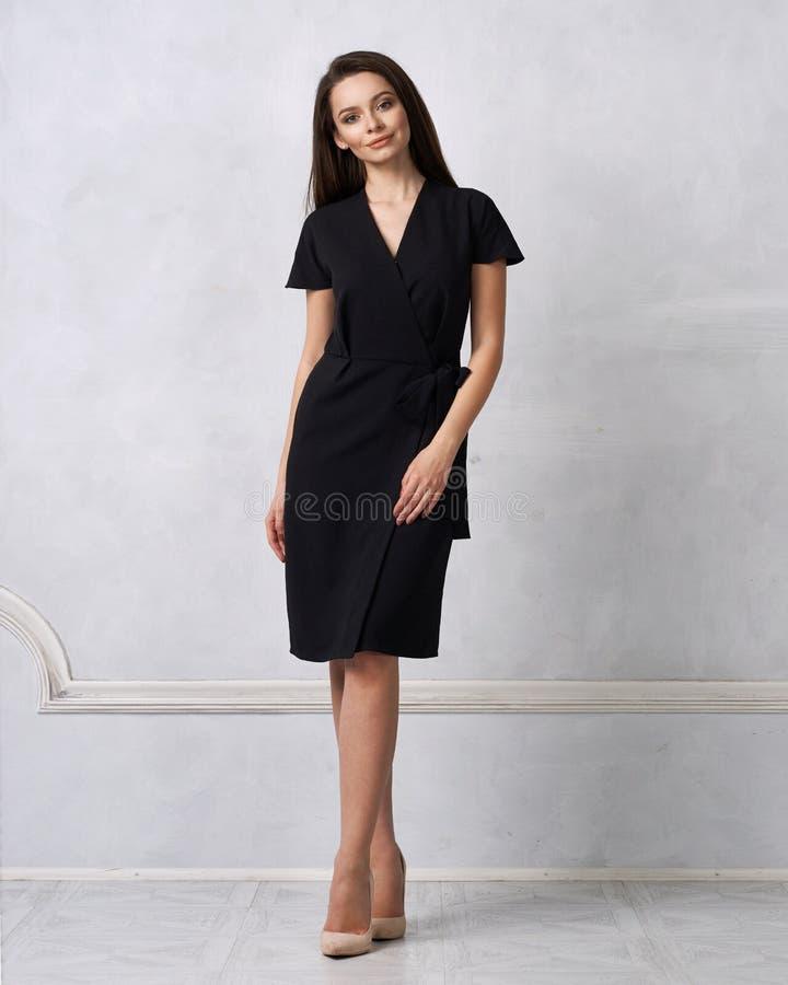 Θηλυκό πρότυπο στο μαύρο περικάλυμμα γύρω από το φόρεμα του Midi στοκ εικόνα