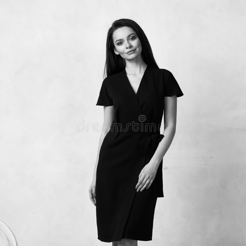 Θηλυκό πρότυπο στο μαύρο περικάλυμμα γύρω από το φόρεμα του Midi στοκ φωτογραφία με δικαίωμα ελεύθερης χρήσης