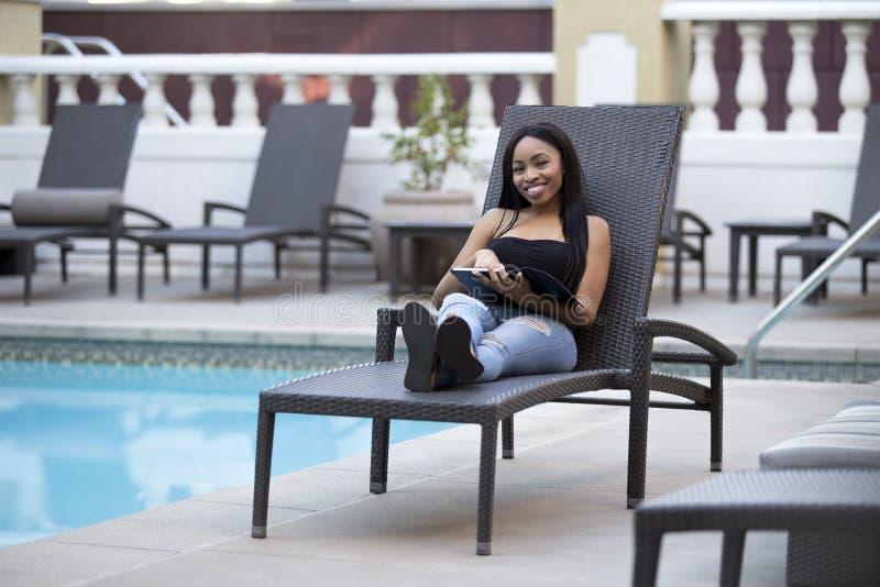 Θηλυκό σε διακοπές που μένουν συνδεμένες με την επιχείρηση με μια ταμπλέτα στοκ φωτογραφία