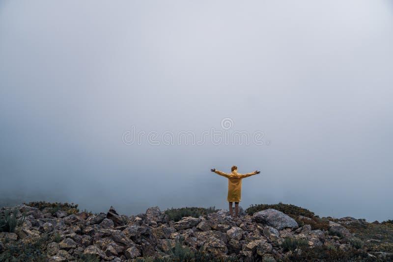 Θηλυκό στο κίτρινο αδιάβροχο, σορτς τζιν που στέκεται στην κορυφή του βουνού με την άποψη των αιχμών στον ορίζοντα Τοπίο Φύση στοκ φωτογραφίες