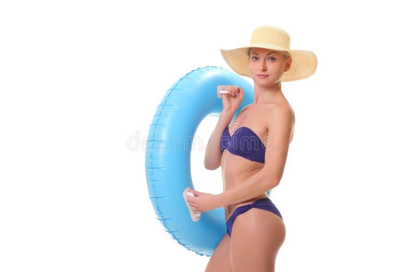 θηλυκό στο κολυμπώντας δαχτυλίδι εκμετάλλευσης μπικινιών στοκ εικόνες
