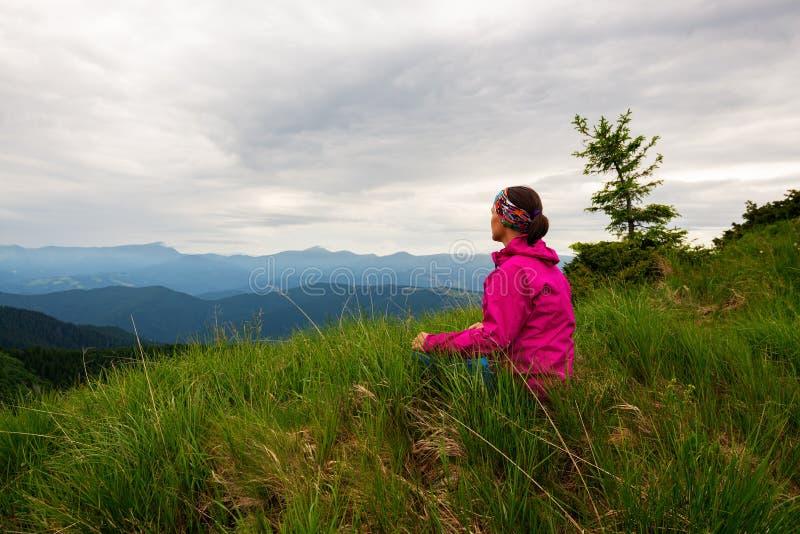 Θηλυκό τυχοδιωκτών που θαυμάζει τις πράσινες κορυφογραμμές στοκ φωτογραφία με δικαίωμα ελεύθερης χρήσης