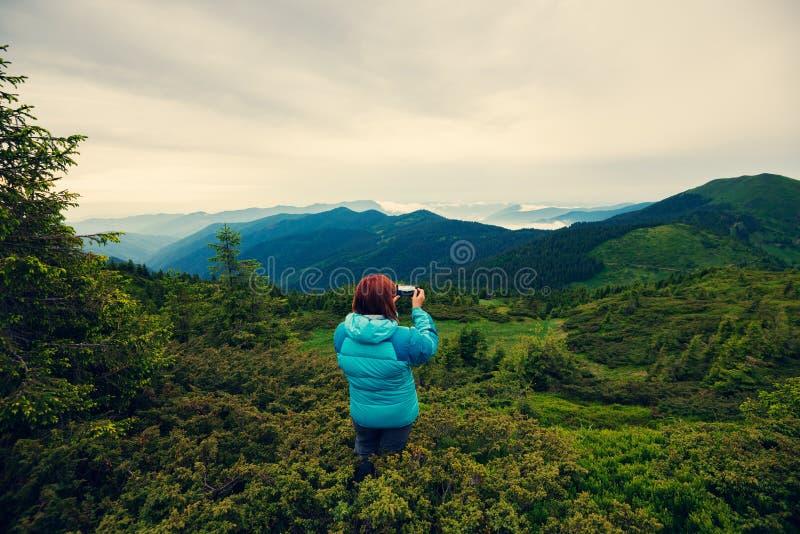 Θηλυκό τυχοδιωκτών που κάνει μια φωτογραφία που χρησιμοποιεί ένα smartphone στοκ φωτογραφία με δικαίωμα ελεύθερης χρήσης
