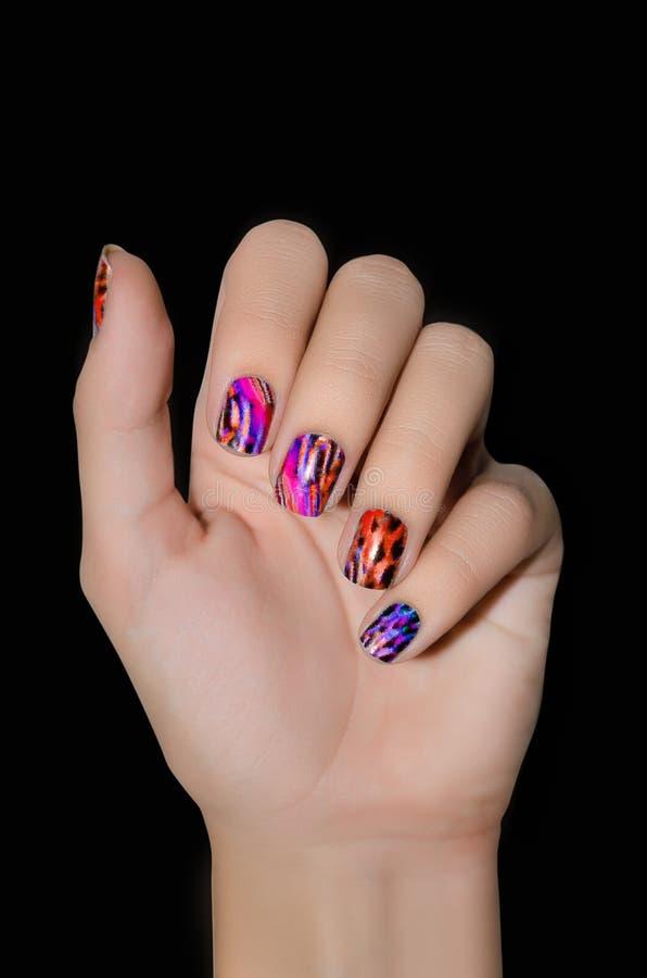 Θηλυκό χέρι με τις αυτοκόλλητες ετικέττες τέχνης καρφιών χρώματος στο μαύρο υπόβαθρο στοκ εικόνα με δικαίωμα ελεύθερης χρήσης