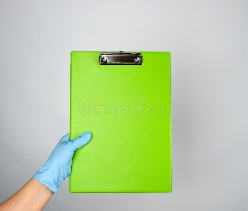θηλυκό χέρι με το μπλε ιατρικό γάντι που κρατά μια πράσινη ταμπλέτα για τη στερέωση των εγγράφων στοκ φωτογραφία με δικαίωμα ελεύθερης χρήσης