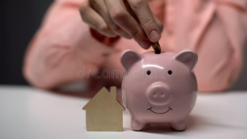 Θηλυκό χέρι που βάζει το νόμισμα στο piggybank, ξύλινο σπίτι παιχνιδιών που στέκεται πλησίον, υποθήκη στοκ φωτογραφία