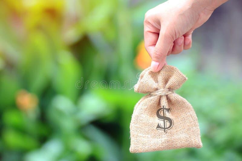 Θηλυκό χέρι που κρατά έναν σάκο των χρημάτων για τις ιδέες εμπορικών συναλλαγών Ή οικονομική επένδυση στοκ εικόνα