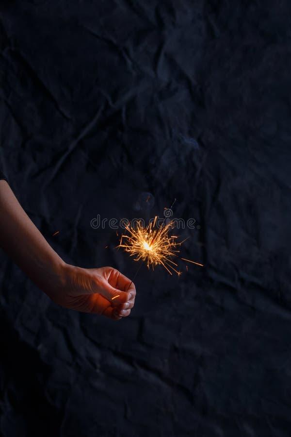 Θηλυκό χέρι που κρατά ένα κάψιμο sparkler Υπόβαθρο διακοπών Χριστουγέννων sparkler για το νέο έτος Χριστουγέννων στοκ εικόνες
