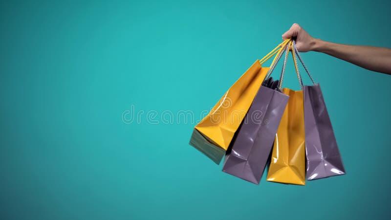 Θηλυκό χέρι που κρατά πολλές ζωηρόχρωμες τσάντες αγορών στο μπλε υπόβαθρο, πρότυπο στοκ εικόνα με δικαίωμα ελεύθερης χρήσης
