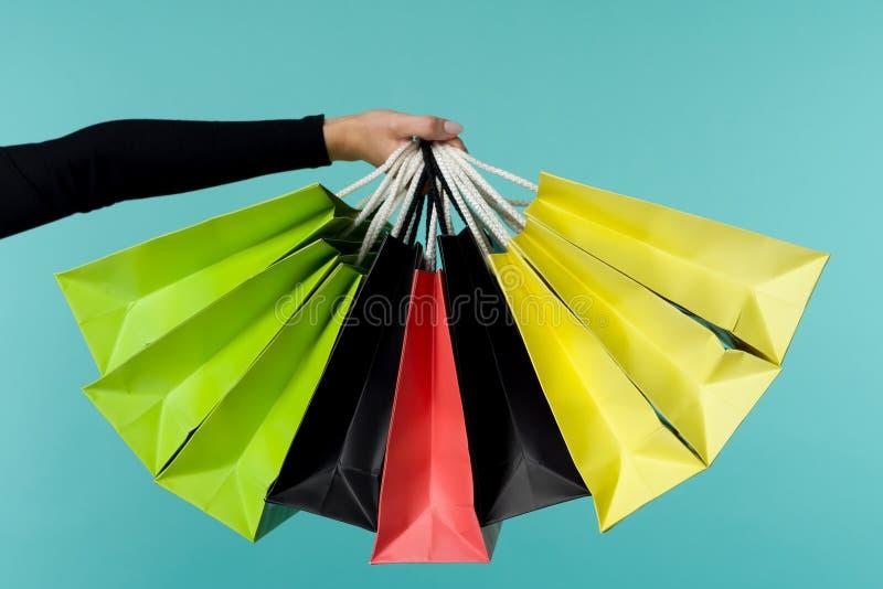 Θηλυκό χέρι που κρατά τις ζωηρόχρωμες τσάντες αγορών Μαύρη έννοια διακοπών Παρασκευής στοκ φωτογραφία με δικαίωμα ελεύθερης χρήσης