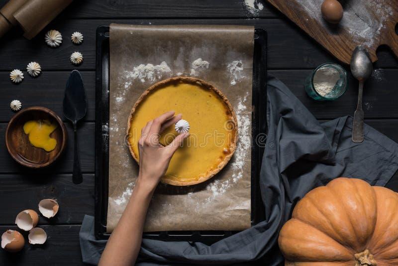 Θηλυκό χέρι που τοποθετεί τη μαρέγκα επάνω στην πίτα στοκ εικόνες