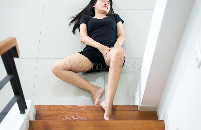 Θηλυκό χεριών σχετικά με το πόδι της που τραυματίζονται, ασιατική γυναίκα που πέφτει κάτω της σκάλας στοκ φωτογραφίες