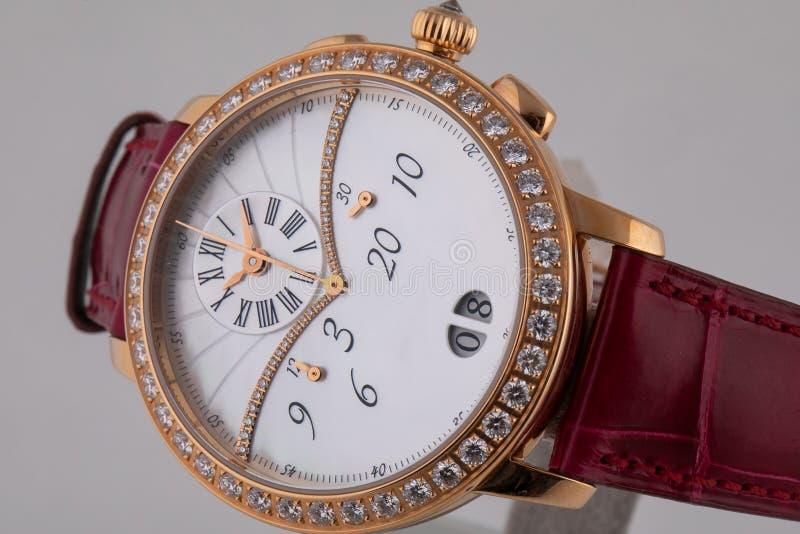 Θηλυκό χρυσό wristwatch με τον άσπρο πίνακα, χρυσό δεξιόστροφα με chronograph burgundy στο λουρί δέρματος που απομονώνεται στο άσ στοκ φωτογραφίες