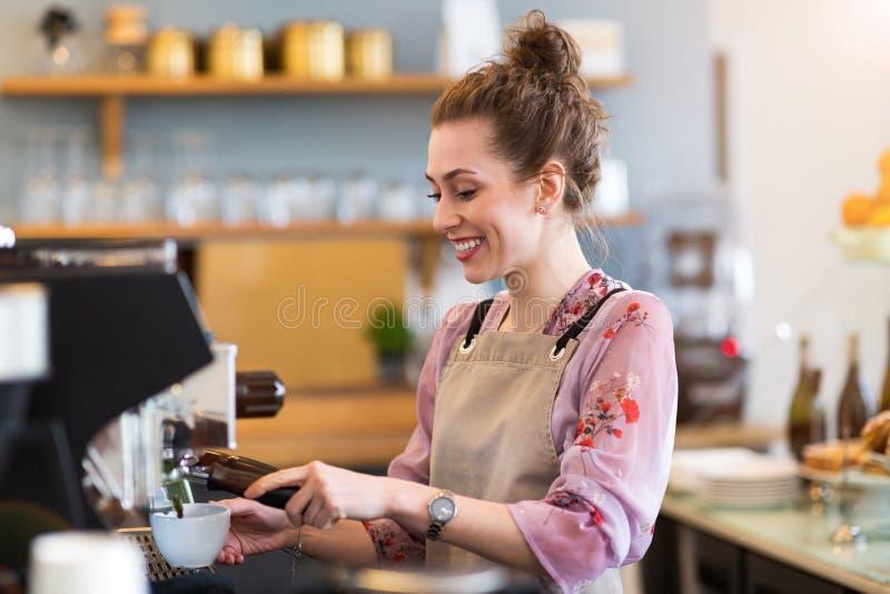 Θηλυκό barista που κατασκευάζει τον καφέ στοκ φωτογραφία