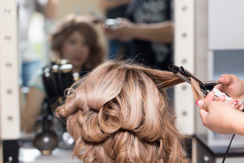 Θηλυκό Hairstyles στο κατσάρωμα σε ένα σαλόνι ομορφιάς στοκ εικόνα