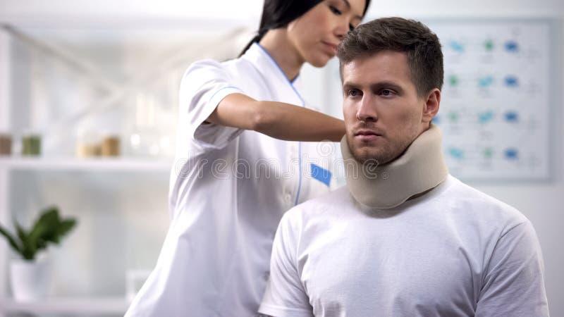 Θηλυκό orthopedist που καθορίζει το αρσενικό υπομονετικό αποτέλεσμα τραύματος περιλαίμιων αφρού αυχενικό, rehab στοκ φωτογραφία