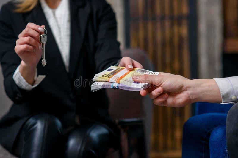 Θηλυκό realtor που δίνει το κλειδί από το επίπεδο, σπίτι ενώ αρσενικοί πελάτες που δίνουν τα χρήματα στοκ φωτογραφία