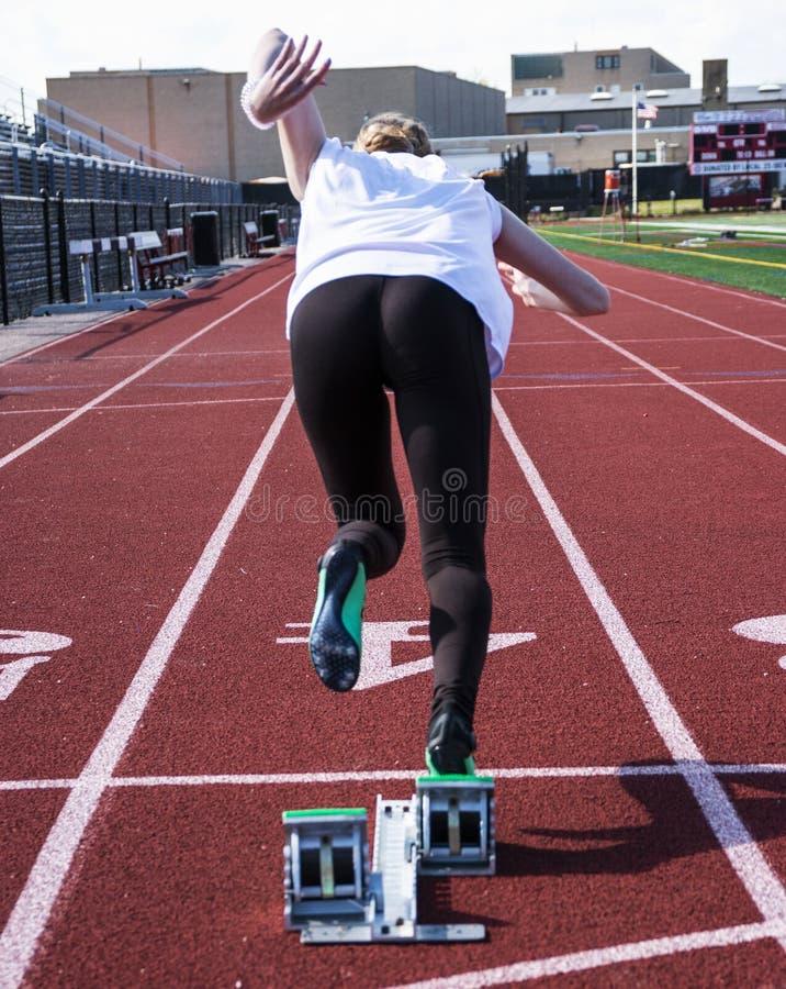 Θηλυκό sprinter που βγαίνει από τους φραγμούς στοκ εικόνες