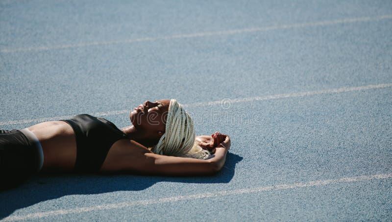 Θηλυκό sprinter που βρίσκεται στο τρέξιμο της διαδρομής μετά από το workout στοκ φωτογραφία